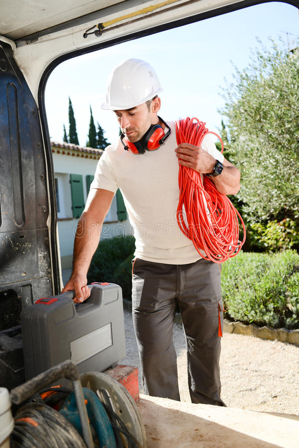 Young electrician artisan taking tools out of professional truck van. Young electrician artisan taking tools out of his professional truck van royalty free stock images