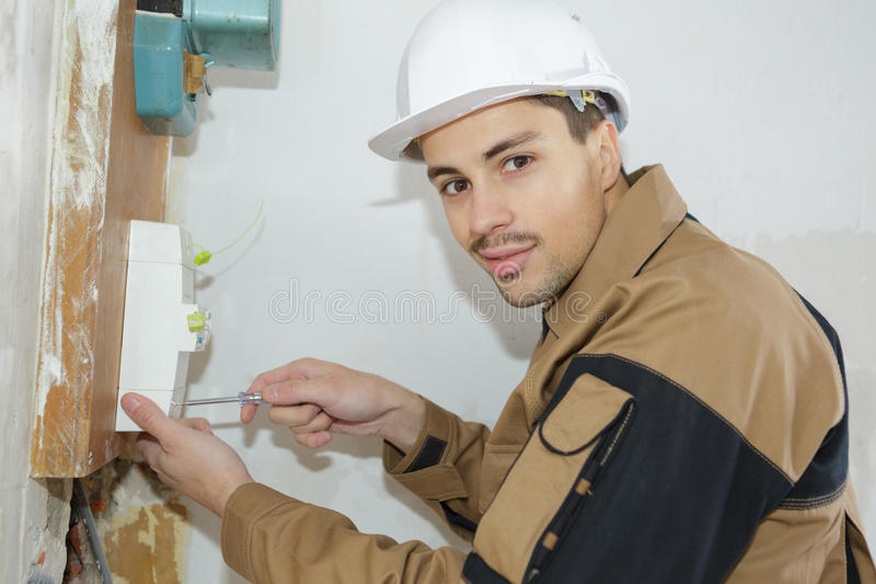 Young electrician builder engineer installing fuse box royalty free stock photography