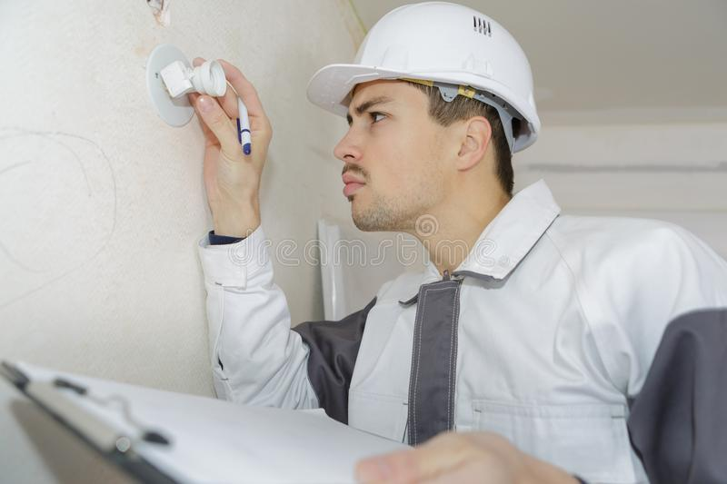 Young electrician changing lightbulb royalty free stock images