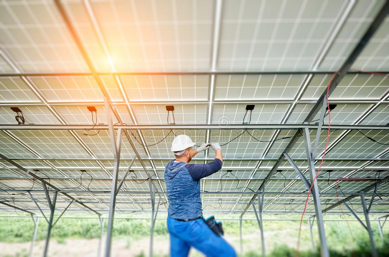 Installing of solar photo voltaic panel system. Young electrician in hard hat and rubber gloves wiring solar photo voltaic modules inside the new installed panel stock photos