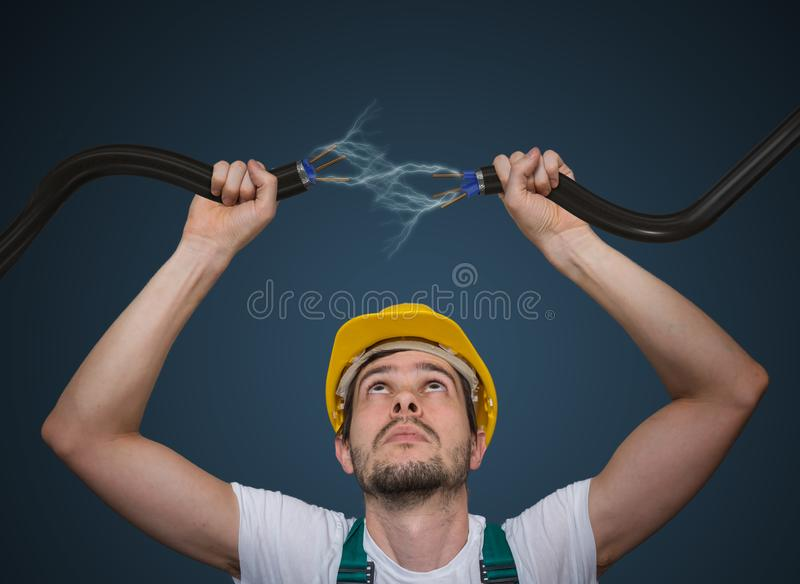 Young electrician holds cables in hands and connecting them. Lightning and electricity around royalty free stock images