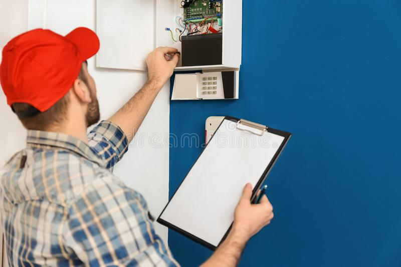 Young electrician installing alarm system royalty free stock photo
