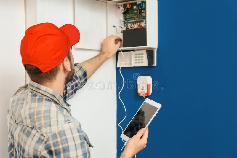 Young electrician installing alarm system royalty free stock images