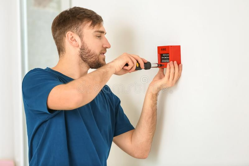 Young electrician installing fire alarm unit on wall stock images