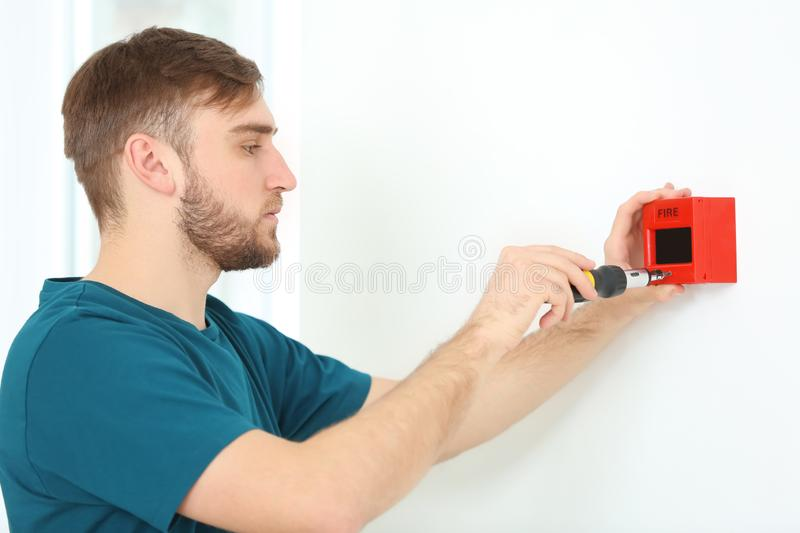 Young electrician installing fire alarm unit on wall stock photos