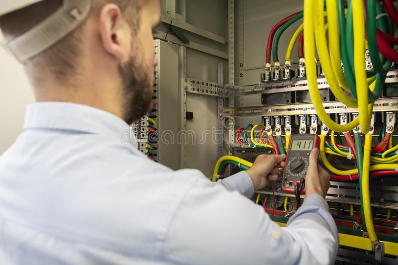 Young electrician measuring voltage in fuse board. Male technician examining fusebox with multimeter probe royalty free stock images