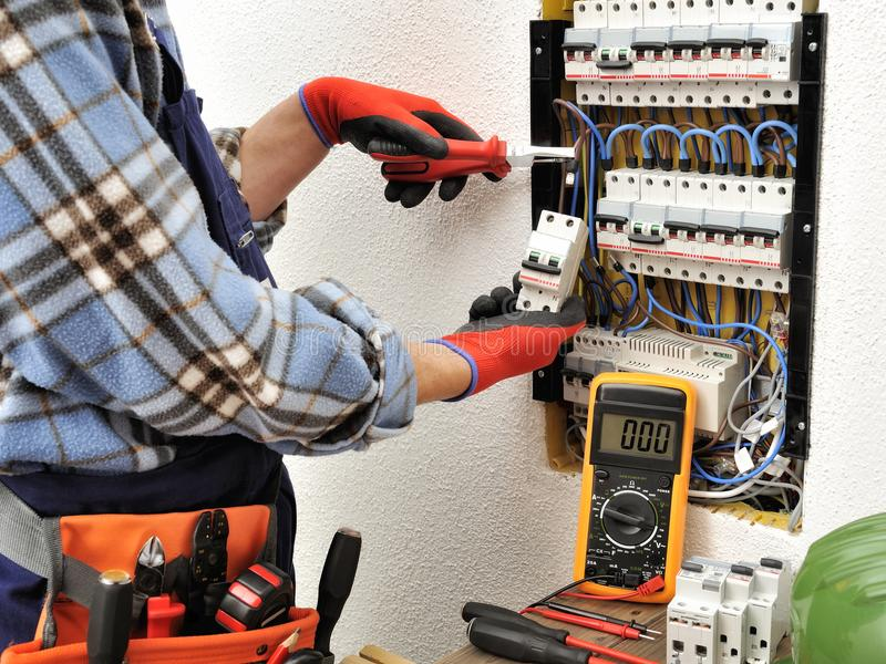 Young electrician technician at work on a electrical panel with royalty free stock images