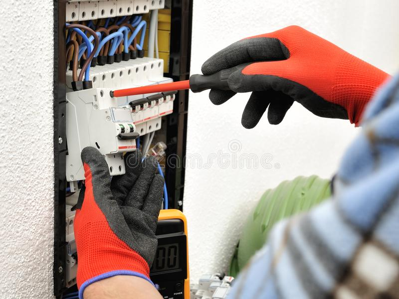 Young electrician technician at work on a electrical panel with stock image