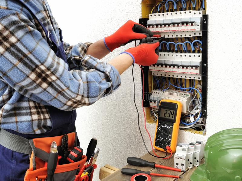 Young electrician technician at work on a electrical panel with stock photo