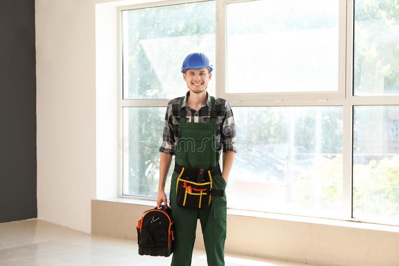 Young electrician with tools bag in empty flat royalty free stock images