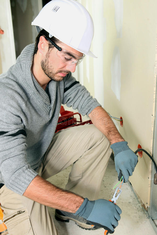 Young electrician using pliers royalty free stock photo