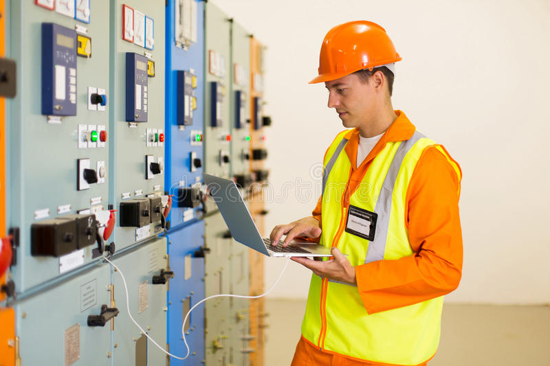 Young electrician working laptop. Experienced electrician working on laptop in substation royalty free stock photos