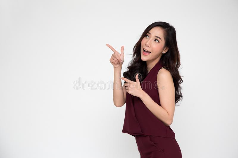 Young elegant Asian woman smiling and pointing to empty copy space  on white background royalty free stock image