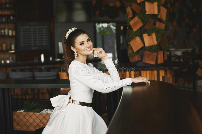 Young elegant beautiful and brunette model woman in white dress with gold belt sitting in bar and waiting for stock photos