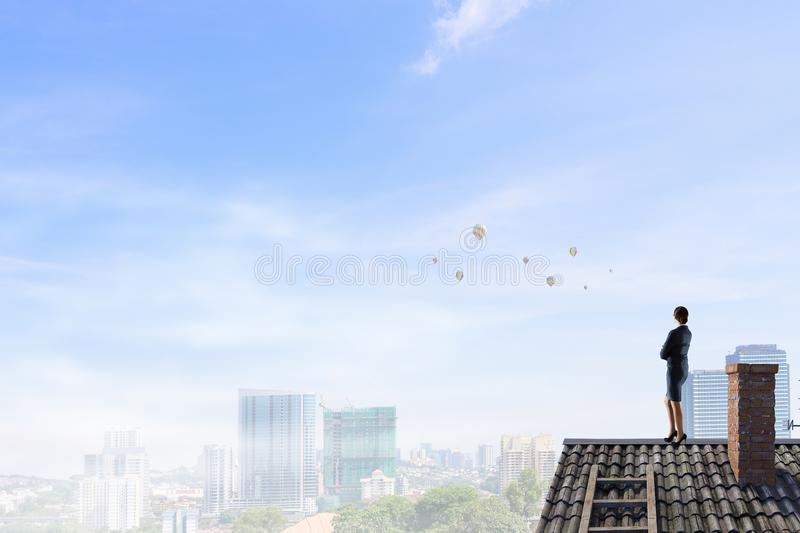 Businesswoman on house roof . Mixed media royalty free stock photos