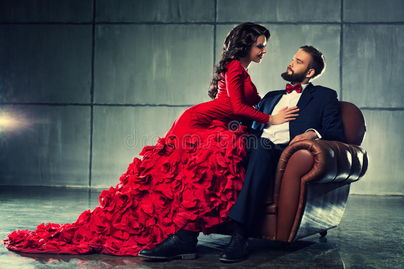 Young elegant couple. Young elegant loving couple in evening dress portrait. Woman in red and men in black suit sitting on chair stock images