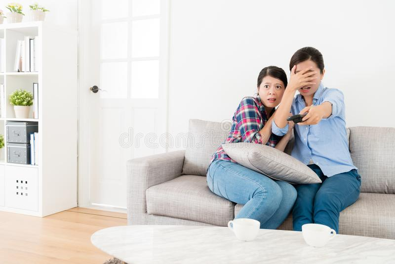 Young elegant female friends watching tv together. And choosing ghost program video feeling afraid when they sitting on sofa couch royalty free stock photography