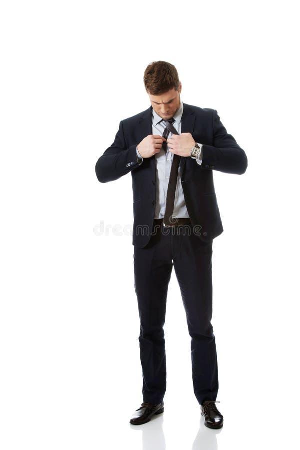 Young elegant man ties necktie. royalty free stock photos