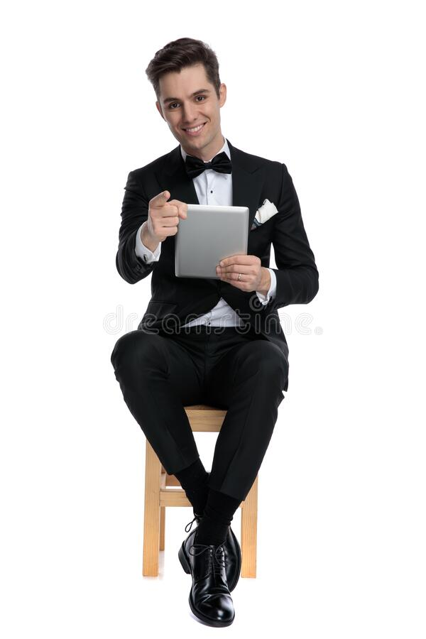 Young elegant man pointing finger and holding tab royalty free stock photography