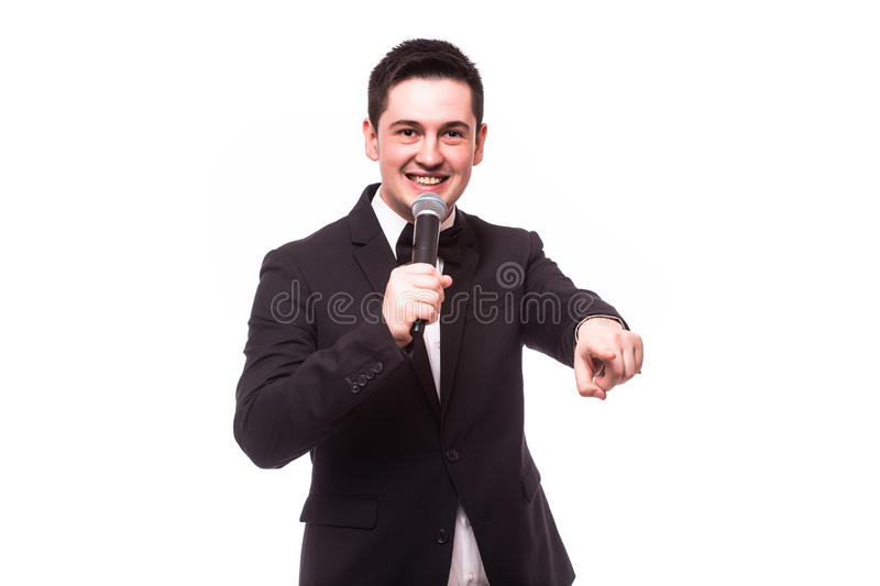 Young elegant talking man holding microphone talking with pointing finger. Isolated on white background. Showman concept stock photo