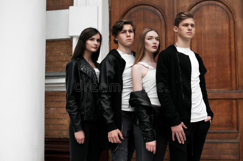 Young elegant trendy friends outdoors, wearing black and white clothing royalty free stock photo