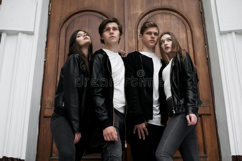 Young elegant trendy friends outdoors, wearing black and white clothing stock photography