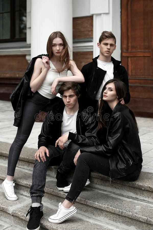 Young elegant trendy friends outdoors, wearing black and white clothing stock image