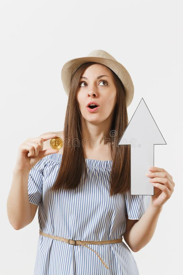 Young elegant woman in blue dress, hat holding bitcoin, coin of golden color, up value arrow isolated on white royalty free stock images