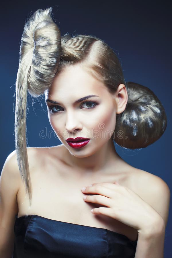 Young elegant woman with creative hair style leopard print close. Up on dark blue background, fashion model halloween selebration royalty free stock photo