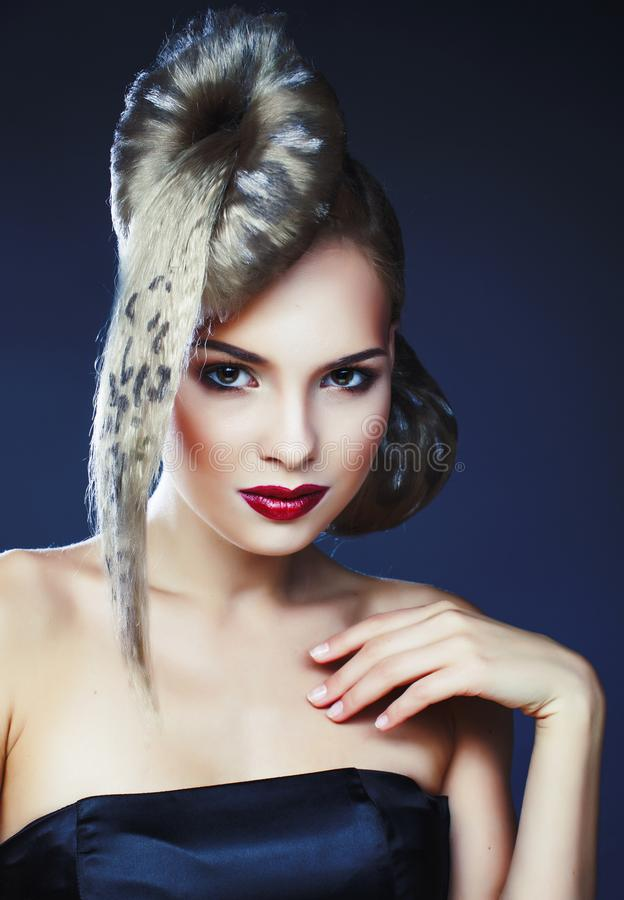 Young elegant woman with creative hair style leopard print close. Up on dark blue background, fashion model halloween selebration stock photo