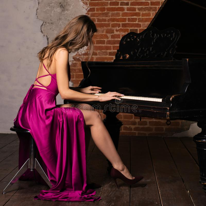Young elegant woman in evening dress with naked back playing piano stock photo