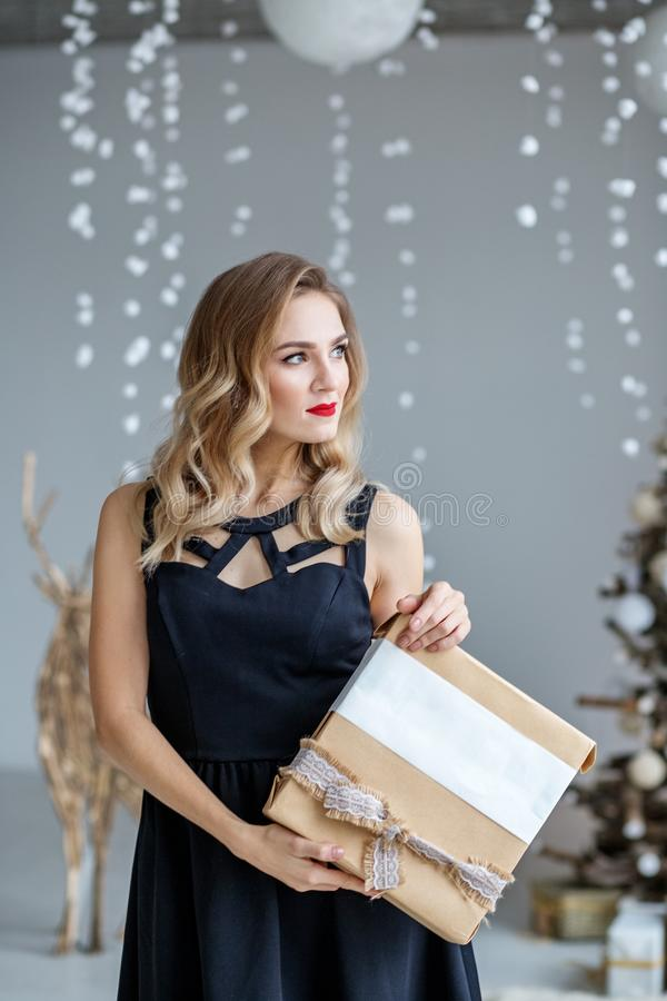 Young elegant woman with a gift box. Concept of Happy Christmas and New Year, winter, party royalty free stock photography