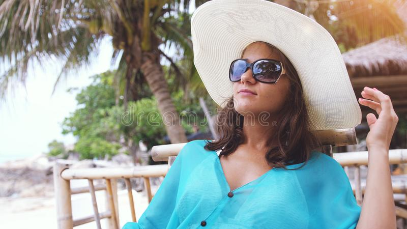 Young elegant woman wearing hat and sunglasses on holiday, sitting in beach cafe stock photo
