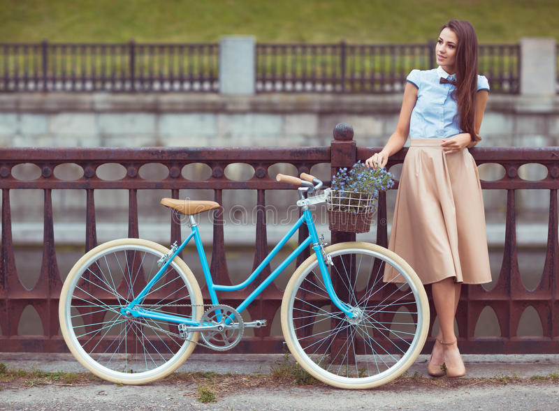 Young elegantly dressed woman with bicycle, summer and lifestyle stock image
