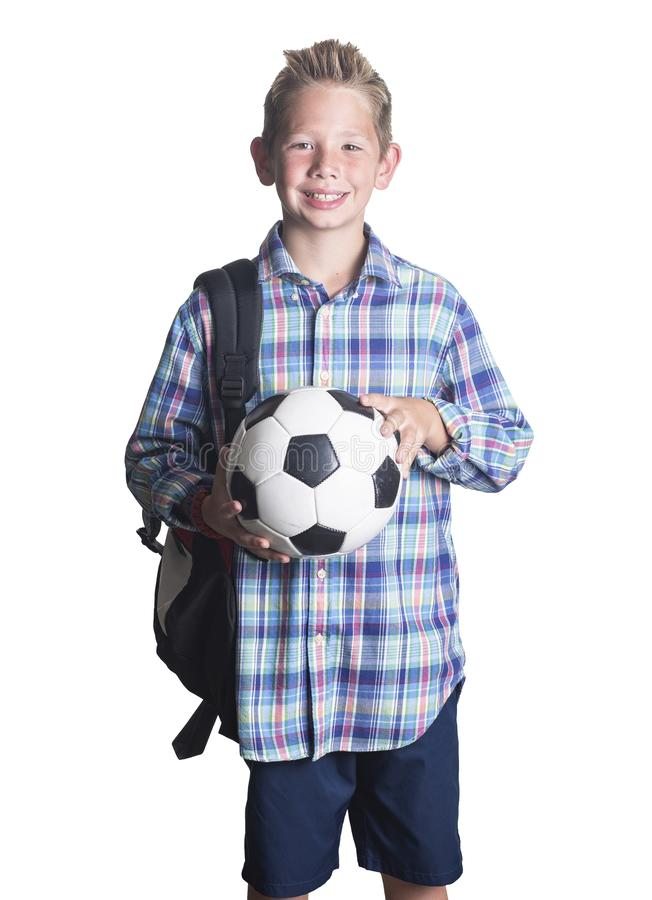 Young elementary school aged boy smiling and holding a soccer ball royalty free stock photo