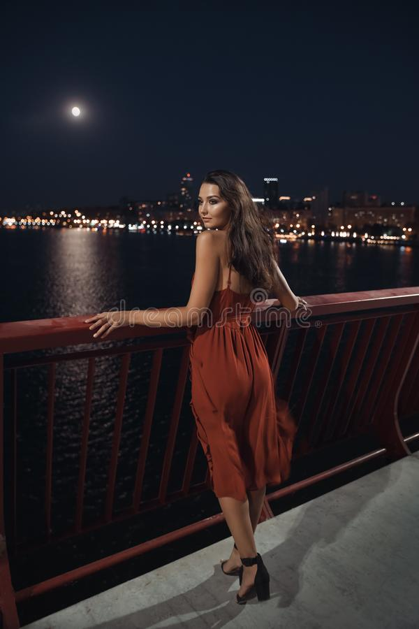 Young ellegant woman standing on the ligths of the night city background. Freedom and girl in love concept royalty free stock images