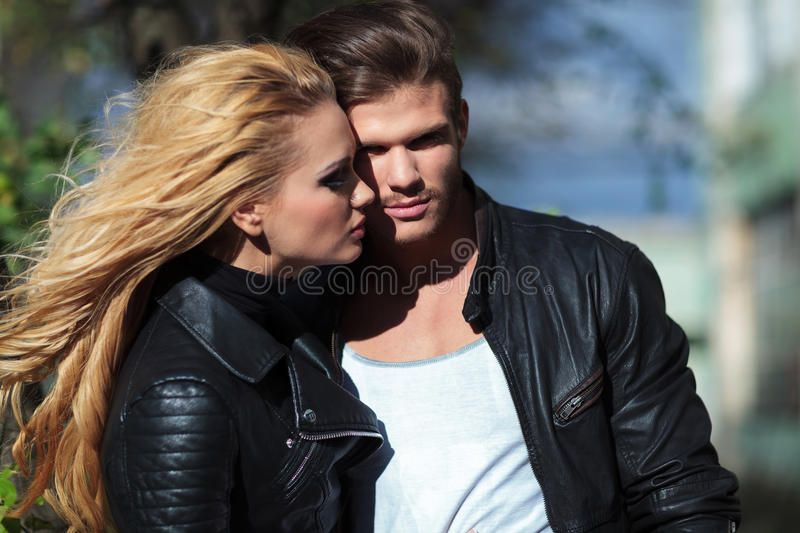 Young embraced fashion couple. Manlooking at the camera and women looking at man royalty free stock image