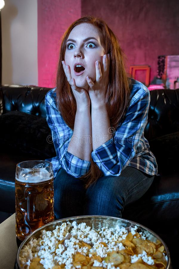 Young emotional attractive woman alone at home sofa couch watchi. Ng excited television football sport match or TV contest eating popcorn cheering crazy fan royalty free stock photos