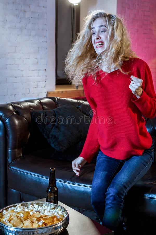 Young emotional attractive woman alone at home sofa couch watchi. Ng excited television football sport match or TV contest eating popcorn cheering crazy fan stock image