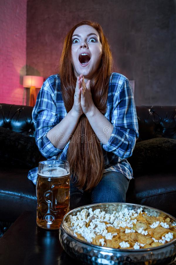 Young emotional attractive woman alone at home sofa couch watchi. Ng excited television football sport match or TV contest eating popcorn cheering crazy fan royalty free stock photo