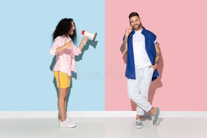 Young emotional man and woman on pink and blue background. Young emotional caucasian couple in bright casual clothes posing on pink and blue background. Concept royalty free stock image