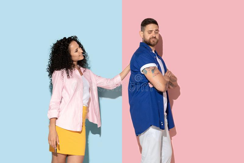 Young emotional man and woman on pink and blue background. Young emotional caucasian couple in bright casual clothes posing on pink and blue background. Concept royalty free stock photo