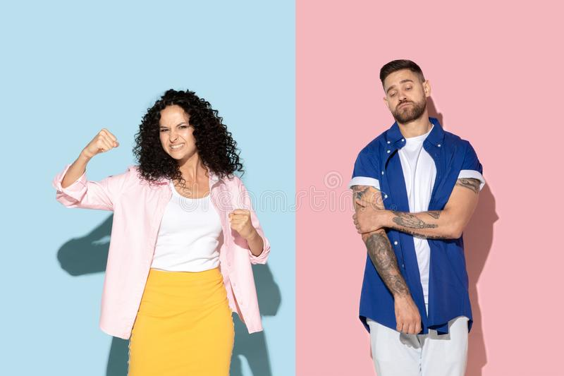 Young emotional man and woman on pink and blue background. Young emotional caucasian couple in bright casual clothes posing on pink and blue background. Concept stock photos