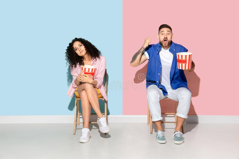 Young emotional man and woman on pink and blue background. Young emotional caucasian couple in bright casual clothes posing on pink and blue background. Concept royalty free stock photos