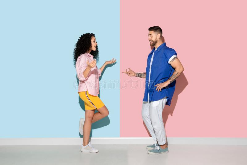 Young emotional man and woman on pink and blue background. Young emotional caucasian couple in bright casual clothes posing on pink and blue background. Concept stock images