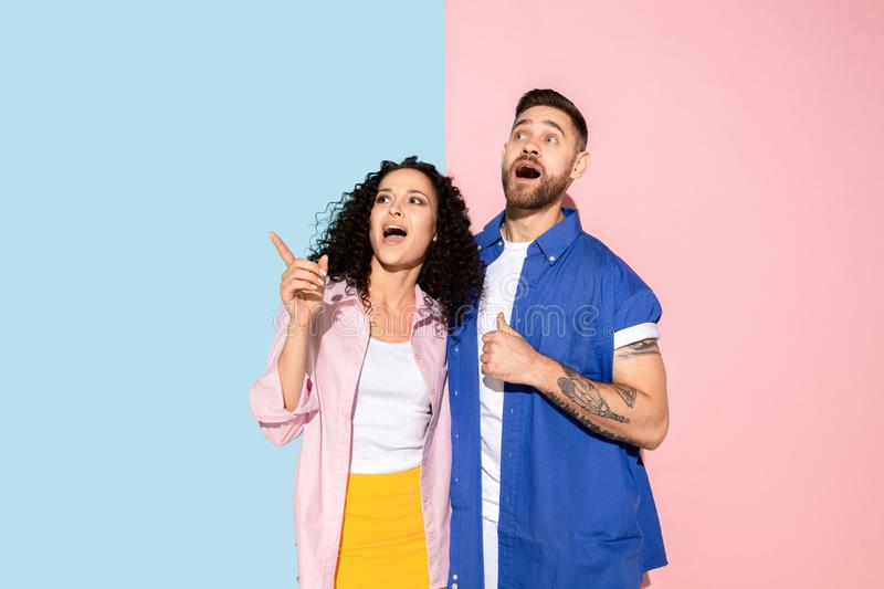 Young emotional man and woman on pink and blue background. Young emotional caucasian couple in bright casual clothes posing on pink and blue background. Concept stock photography