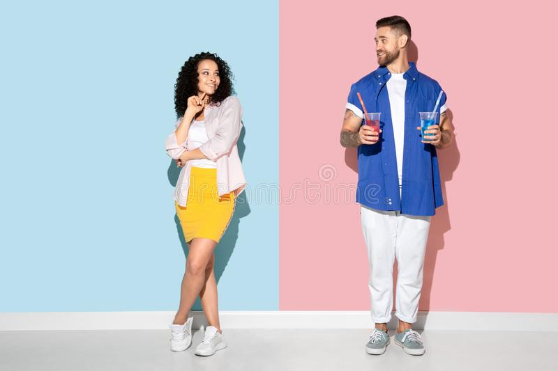 Young emotional man and woman on pink and blue background. Young emotional caucasian couple in bright casual clothes posing on pink and blue background. Concept stock image