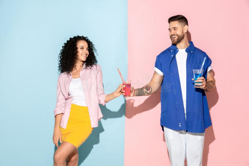 Young emotional man and woman on pink and blue background. Young emotional caucasian couple in bright casual clothes posing on pink and blue background. Concept stock photo