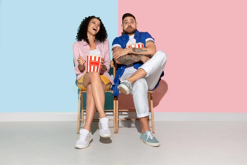Young emotional man and woman on pink and blue background. Young emotional caucasian couple in casual clothes posing on pink and blue background. Concept of stock photo