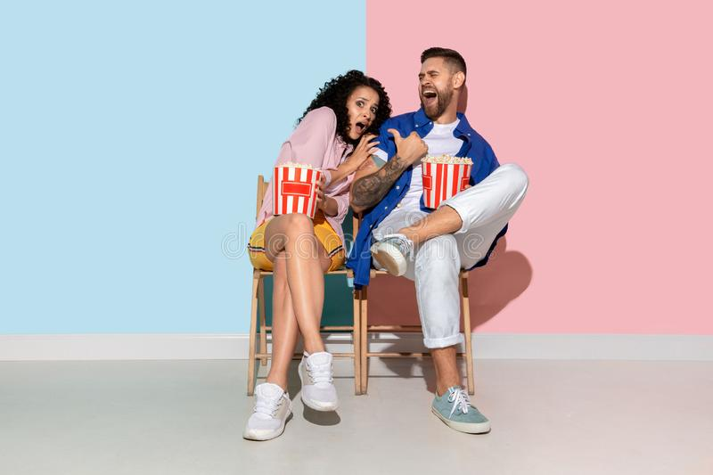 Young emotional man and woman on pink and blue background. Young emotional caucasian couple in casual clothes posing on pink and blue background. Concept of royalty free stock photography